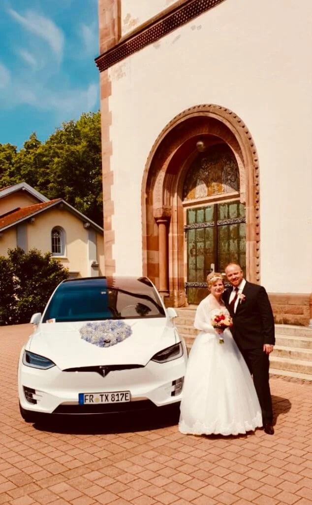 Tesla Model X 100D mieten in Freiburg als Hochzeitsauto vorne mit Brautpaar