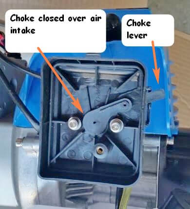 Fully closed choke lever on a small two stroke engine.