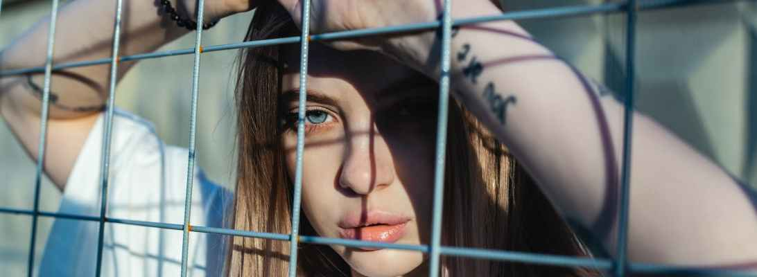 photo of woman leaning on screen fence