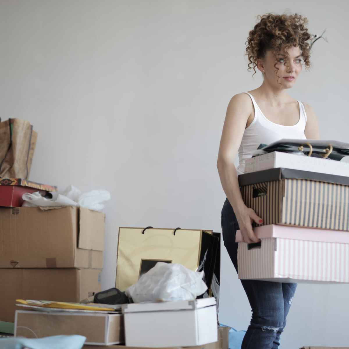 concentrated woman carrying stack of cardboard boxes for relocation