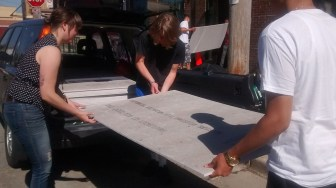 Students and staff unloading the cement board from the car.