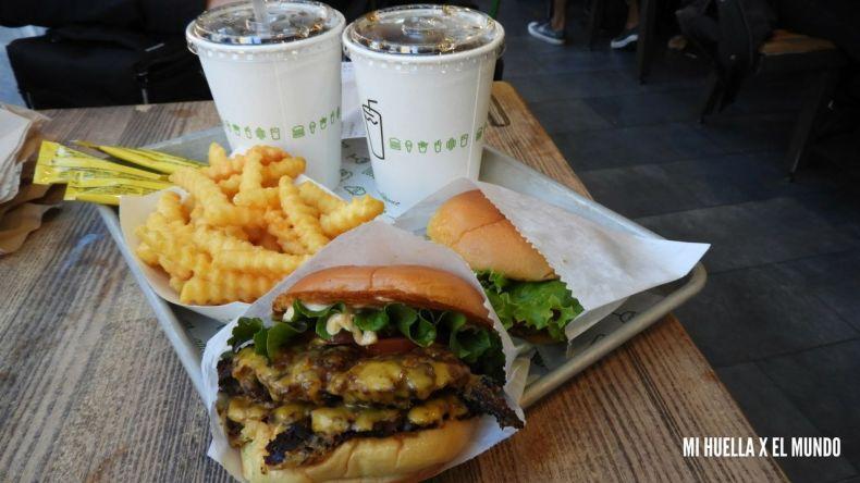 dos hamburguesas con queso lechuga y tomate, unas patatas fritas onduladas y dos coca colas que tomamos en Shake Shack