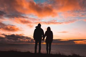 couple holding hands watching sunset