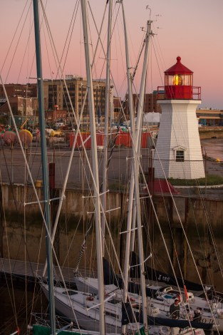 Boats Docked in Front of Lighthouse Photograph