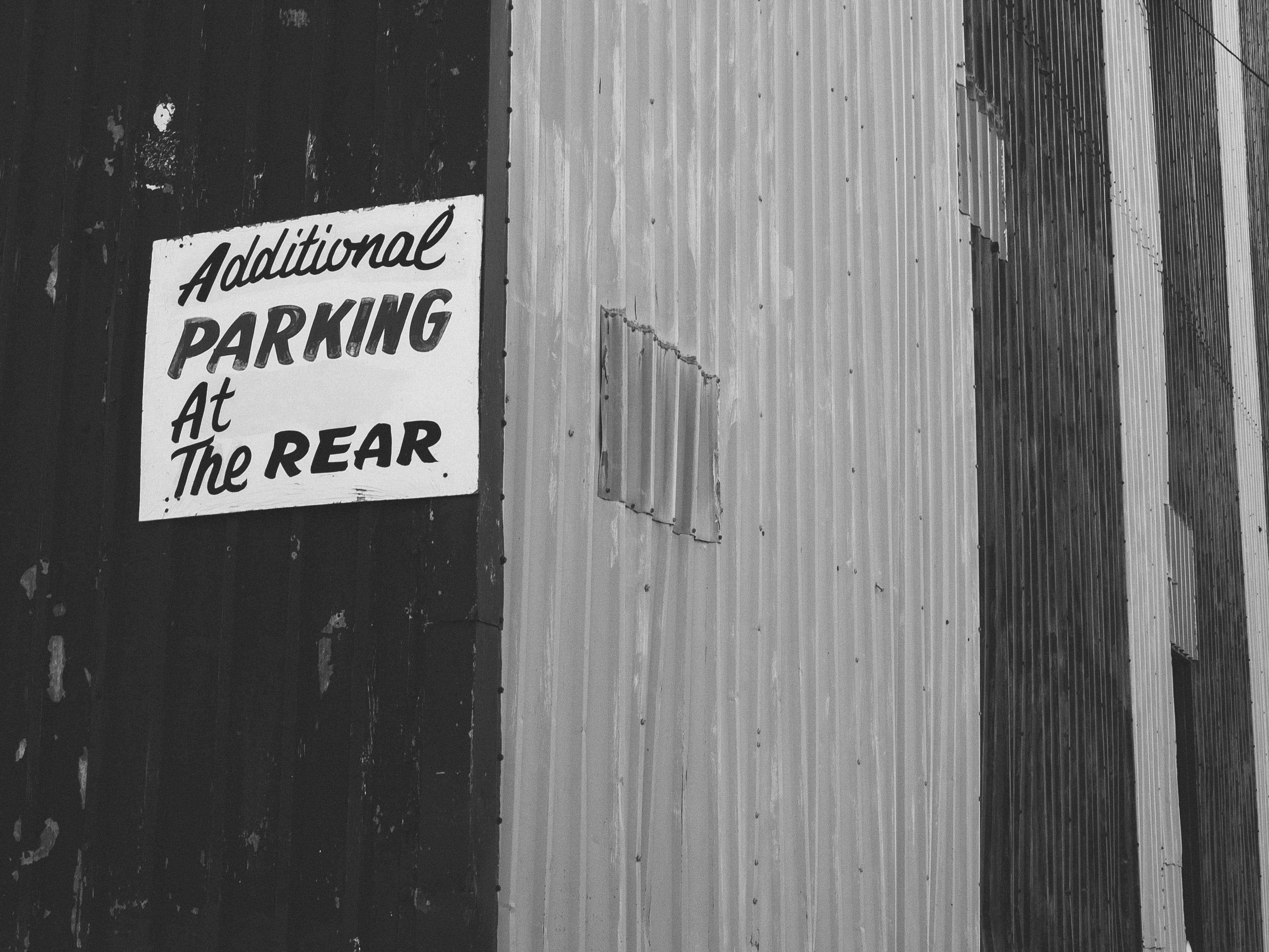 A photograph depicting Hay Market Square Bowling Alley Parking Sign Bw