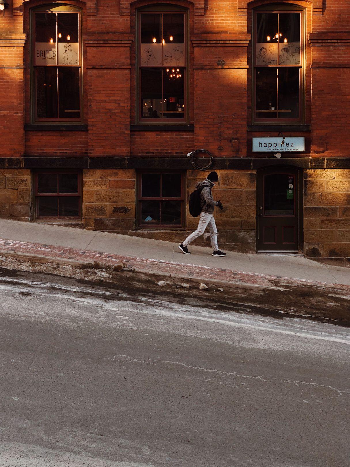 A photo of Man walks by Happinez Bar