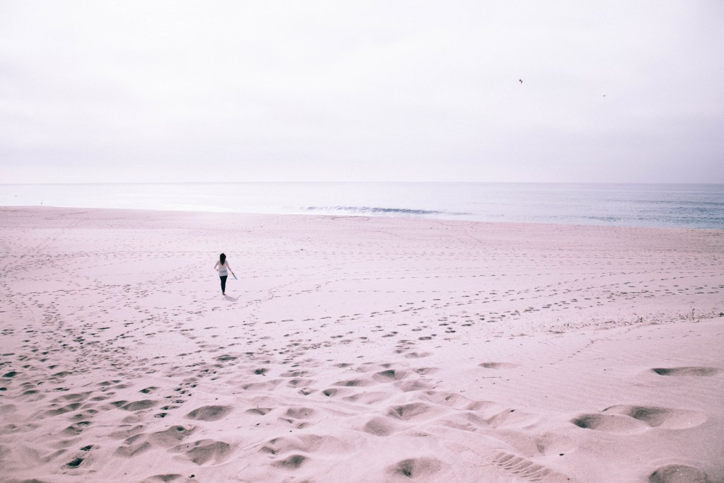 Girl walking across foggy beach in northern Portugal
