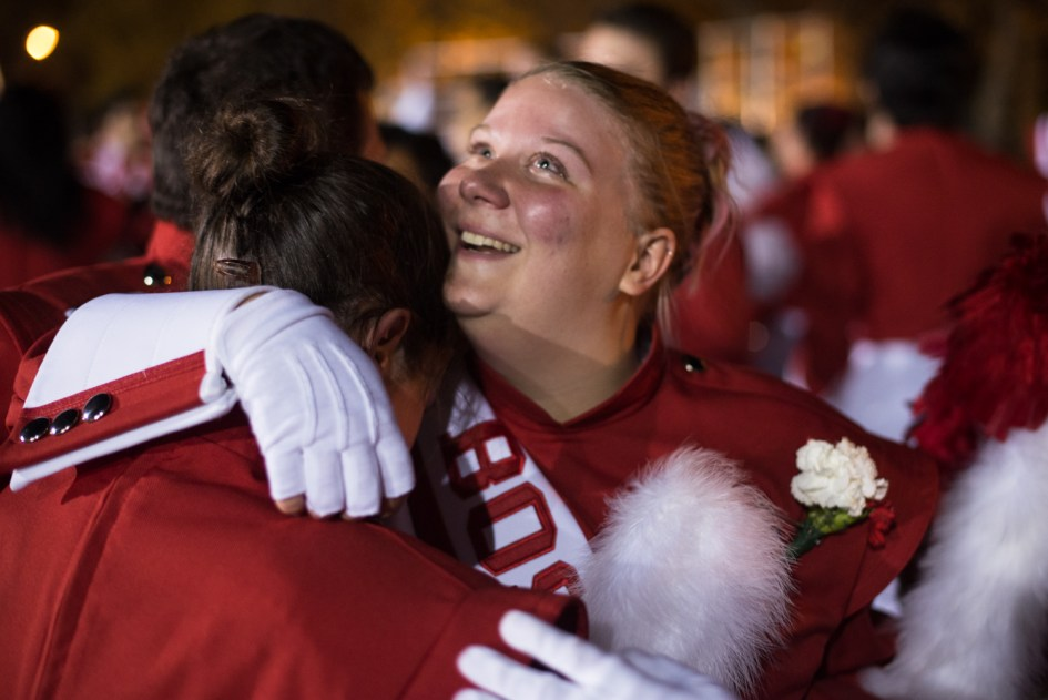 Taylor Kenyon (right) hugs a friend among fellow BU band members gathering following her last performance as a college marching band member.
