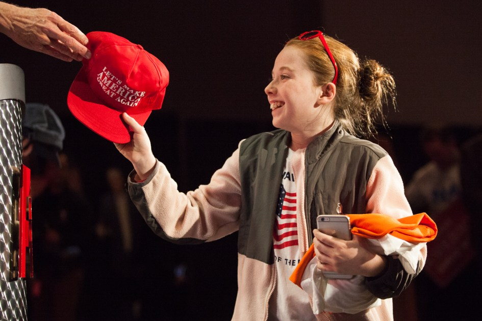 "Braintree, MA – Nov. 8, 2016 – A young audience member receives a free ""Make America Great Again"" hat after correctly answering a trivia question at the Massachusetts Trump-Pence Campaign victory party. Trump supporters gathered at the F1 Boston race track to cheer on their nominee as he was elected 45th president of the United States."