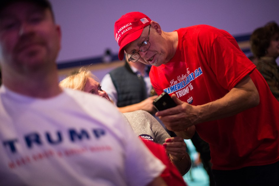 Braintree, MA – Nov. 8, 2016 – Ray Bourbeau, of Chicopee, Massachusetts, reads the latest victory prediction for United States presidential candidate Donald Trump on his phone during the Massachusetts Trump-Pence Campaign victory party. Trump supporters gathered at the F1 Boston race track to cheer on their nominee as he was elected 45th president of the United States.