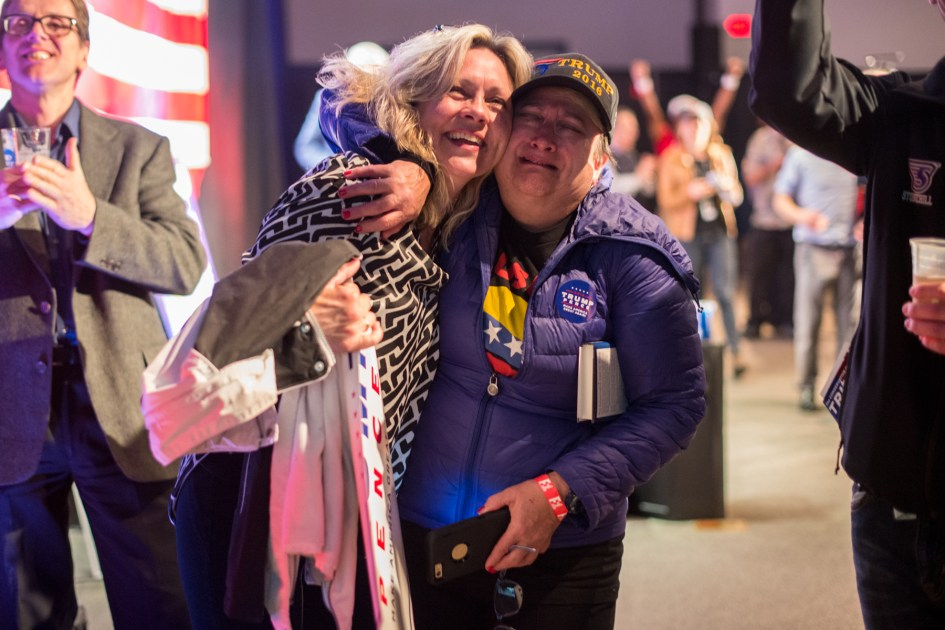 Braintree, MA – Nov. 8, 2016 – Susan Tittle, left, embraces Debbie Makowski as United States presidential election results are reported on Fox News during the Massachusetts Trump-Pence Campaign victory party. Trump supporters gathered at the F1 Boston race track to cheer on their nominee as he was elected 45th president of the United States.
