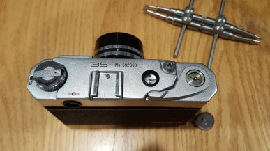 "To remove the top plate for cleaning the viewfinder, use a lens spanner to remove the disc on top of the wind lever and jam a screwdriver into the film ""fork"" inside the film compartment and unscrew the rewind knob."