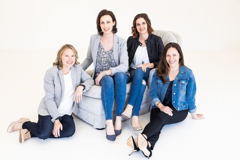 atlanta small business portrait female entrepreneurs sitting on couch wearing complementary outfits white wall studio Woodstock