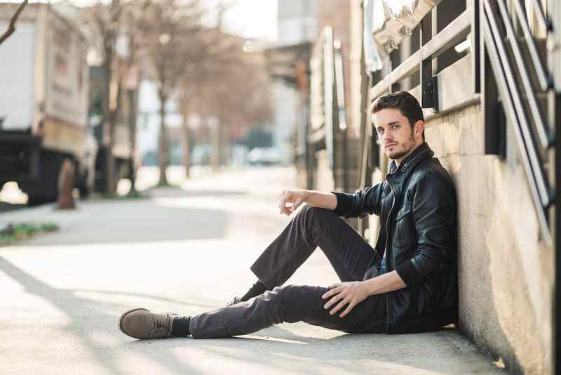 atlanta male actor wears leather jacket and sits on sidewalk of west midtown