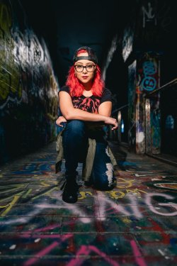 punk girl kneels on graffiti walkway of krog street tunnel atlanta