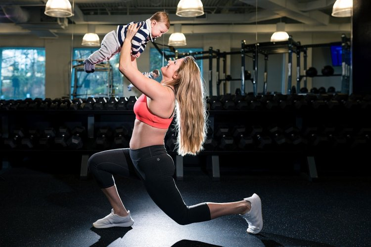 workout mom lifts son in gym
