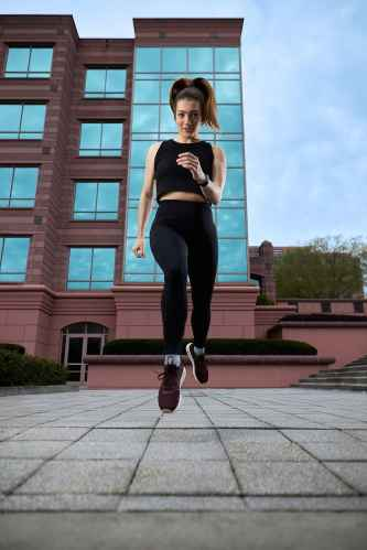 female athlete leaps in urban setting