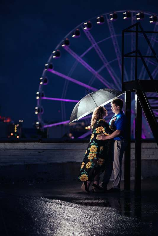 engaged couple under umbrella at night