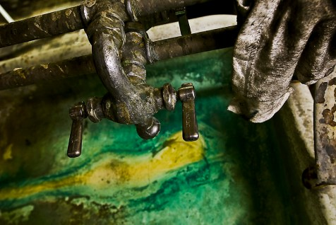 This faucet continues to drip water every few seconds, creating a pull of calcifying water and decaying porcelain in sink basin. Ink stained rags, plastic gloves and greasy fixtures fill the sink, floors and shelves of this bathroom which appears to have gone unused for many years.