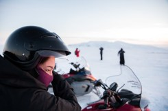Annie struggles to take off her snowmobiling helmet. Photo by Mike Higdon.
