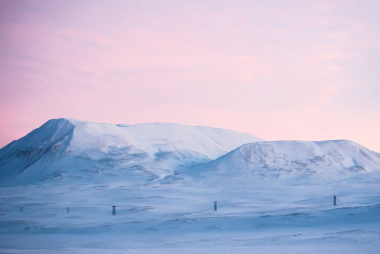 The countryside of Iceland continues to grow more eerie and alien as we separate from civilization. Large areas blanketed in snow. During sunset, the sky changes from white to pink, creating even more unusual, dream-like landscapes. Photo by Mike Higdon