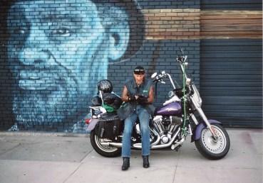 Jack sits on his Harley Davidson motorcycle behind Junkee Clothing Exchange. Joe C. Rock's newest murals is behind him. Photo by Mike Higdon