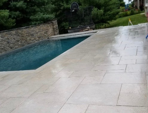 New Pool Installation With Paver Deck and Stone Wall Feature