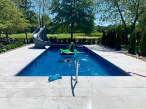 In ground rectangle pool with slide and pavers