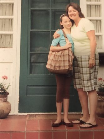 Emma Pound and Lee Pound standing our our porch in front of a green door on Emma's first day of junior high school. I think