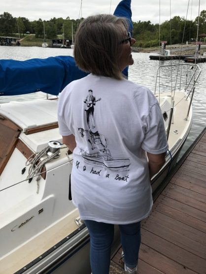 "Lee Pound standing on a dock next to a sailboat. She is wearing a white Lyle Lovett ""If I had a boat"" t-shirt. Her back is to the camera so you can see what is on the t-shirt."