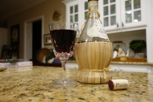 A picture of a opened bottle of Chianti with a glass of wine sitting in front of the bottle and the cork next to the bottle