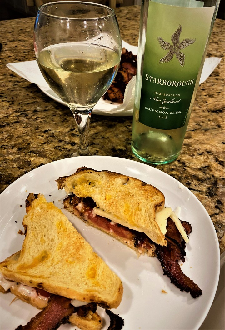 a blt sitting on a white plate. Behind the plate with the BLT is a glass of white wine with the bottle in which in came from next to it.