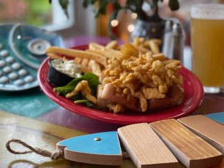 Fried clam strips without bellies piled into a buttery, grilled bun with fries and tartar sauce on the side