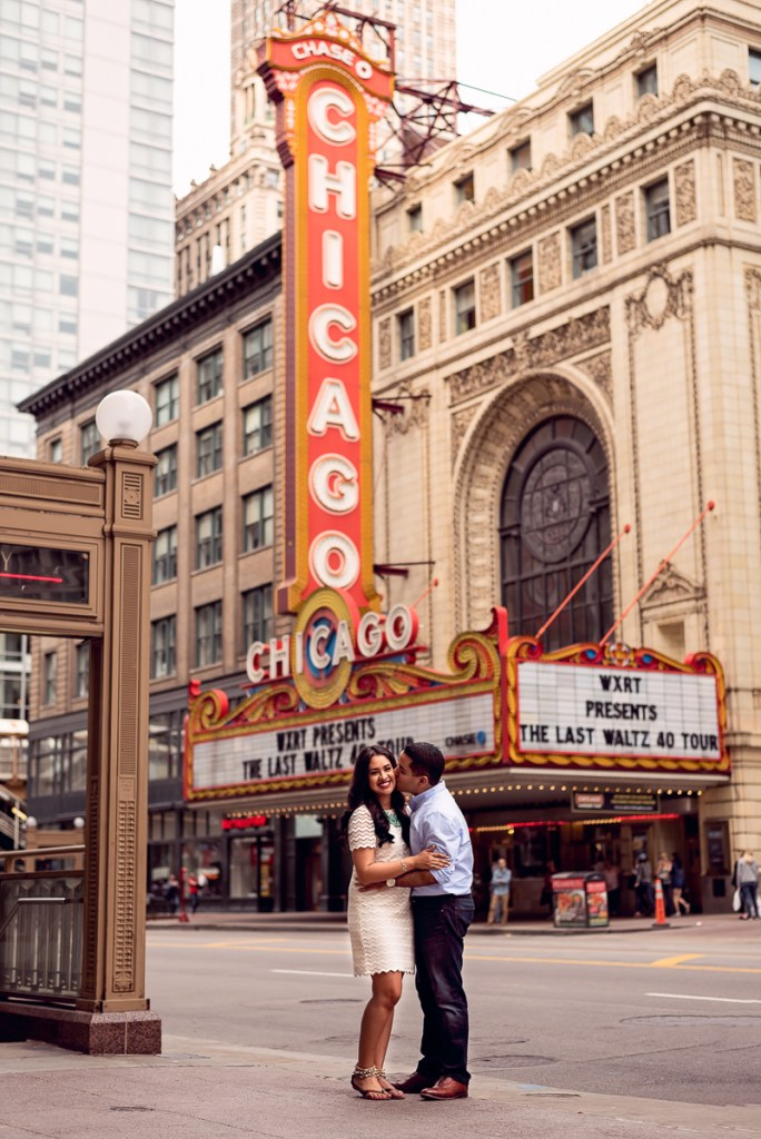 An engagement session for an engaged couple at the Chicago Theater sign in the summer by a wedding photographer Mila Craila Photography