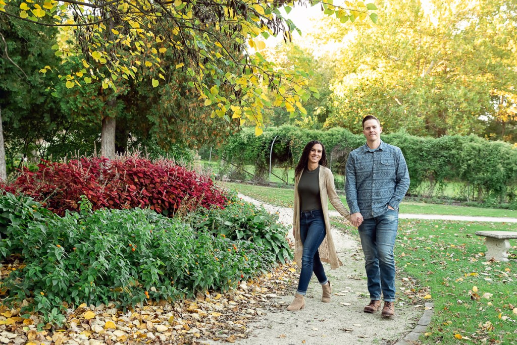 An engagement session for an engaged couple walking at Fabyan Forest Preserve in the fall by a wedding photographer Mila Craila Photography