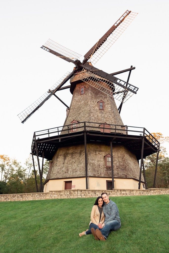 An engagement session for an engaged couple sitting near the windmill at Fabyan Forest Preserve in the fall by a wedding photographer Mila Craila Photography