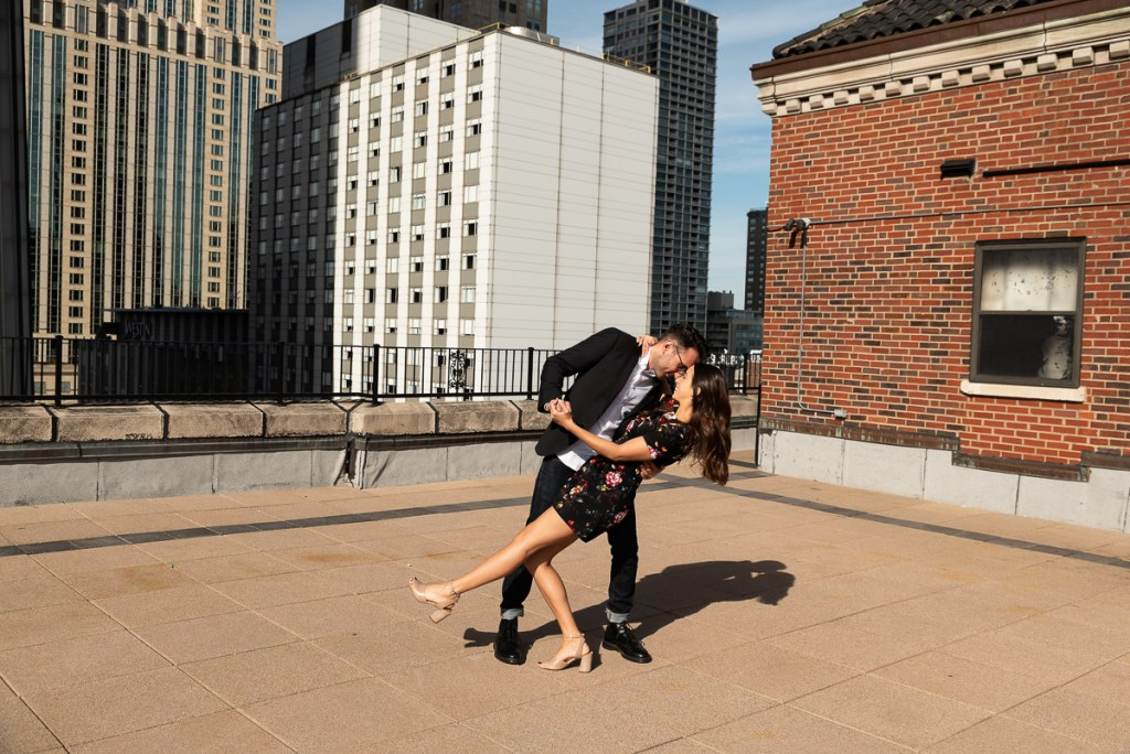 An engagement session for an engaged couple dancing in downtown Chicago in the fall by a wedding photographer Mila Craila Photography