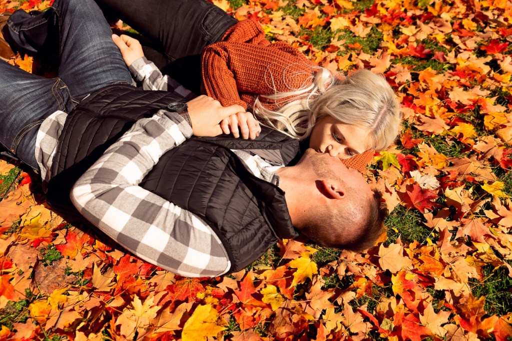 An engagement session for an engaged couple kissing on the ground at Cantigny Park in Wheaton in the fall by a wedding photographer Mila Craila Photography