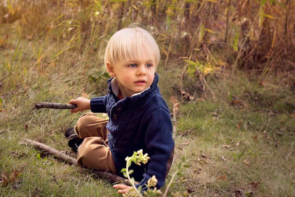 Family session for a little boy holding a wooden stick at Lincoln Park Zoo in Chicago in the fall by family photographer Mila Craila Photography