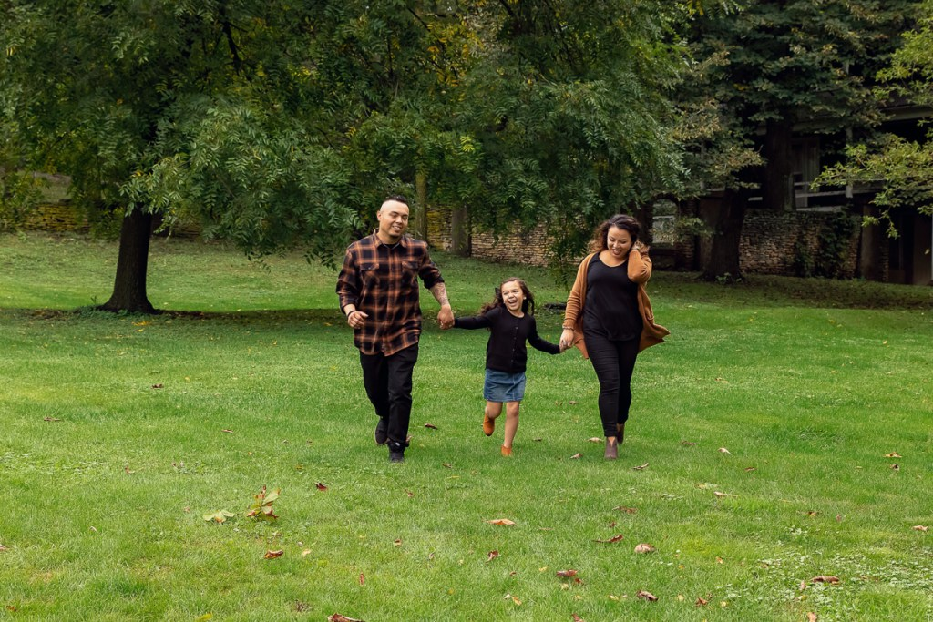 Family session for parents and a young daughter running at Fabyan Forest Preserve in Geneva by family photographer Mila Craila Photography