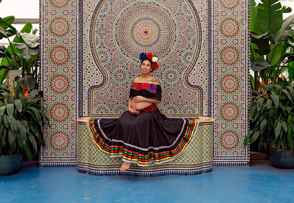 A maternity session for a pregnant woman in a traditional Mexican dress in Garfield Park Conservatory by a maternity photographer Mila Craila Photography
