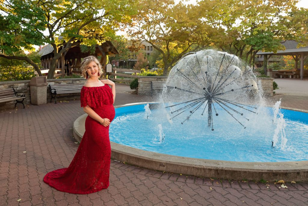 A maternity session for a pregnant woman in a red dress near the fountain on Naperville Riverwalk by a maternity photographer Mila Craila Photography