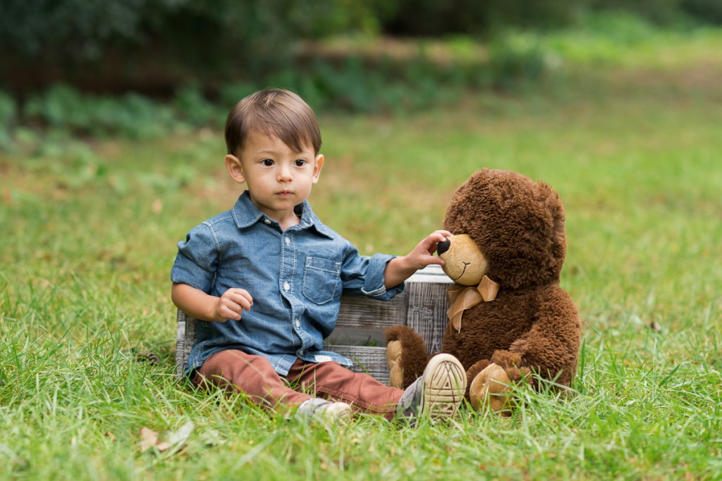 Toddler boy with a stuffed brown bear in a park by family photographer Mila Craila Photography