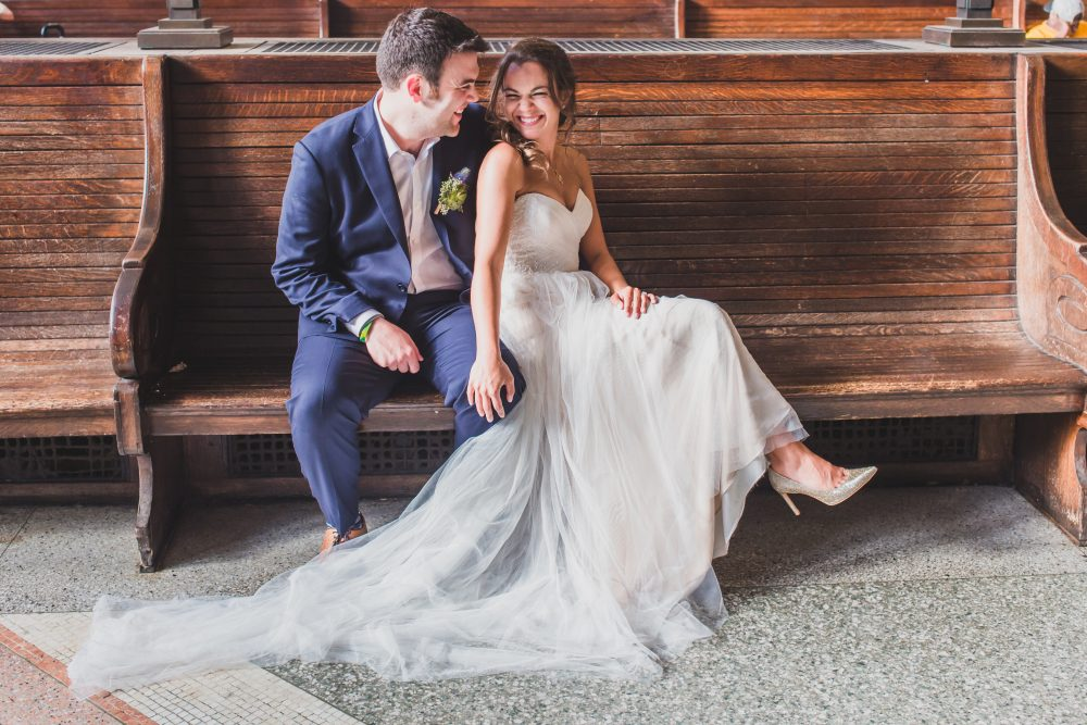 Couple on bench in blue suit and wedding dress looking at each other