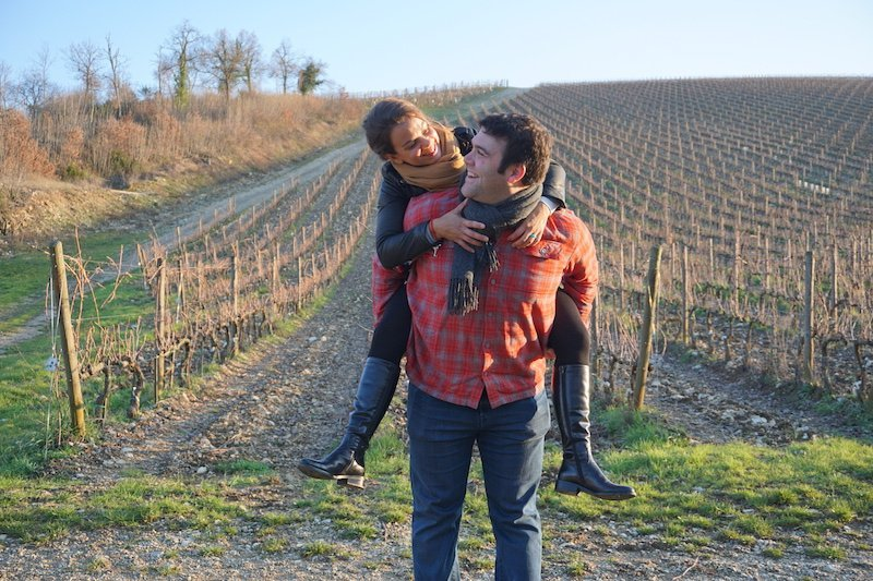 Couple in Vineyard Tuscany at Sunset Woman on Man's Back Looking at Each Other