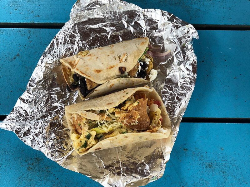 Migas tacos in Austin on tinfoil on Blue Wood backdrop