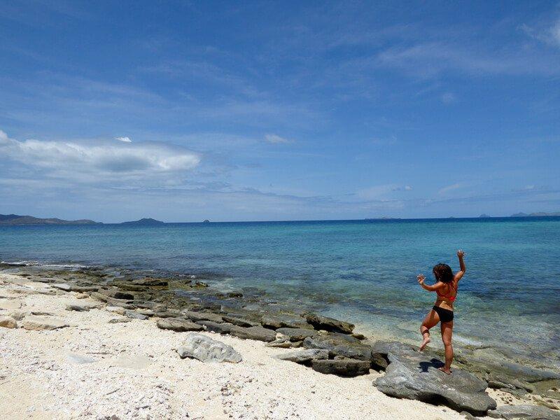 Girl on rocks on white sand beach Fiji with ocean in background island Navini
