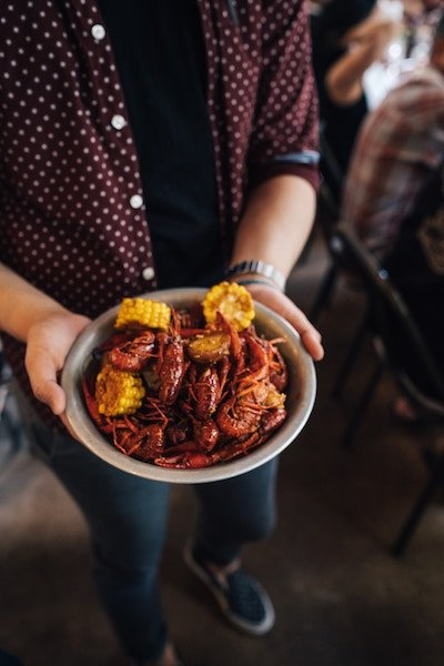 Man holding plate of crawfish
