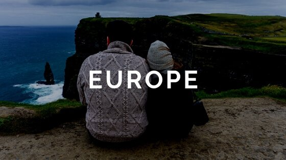 Couple sitting backs facing camera on cliff with water below Europe text overlay