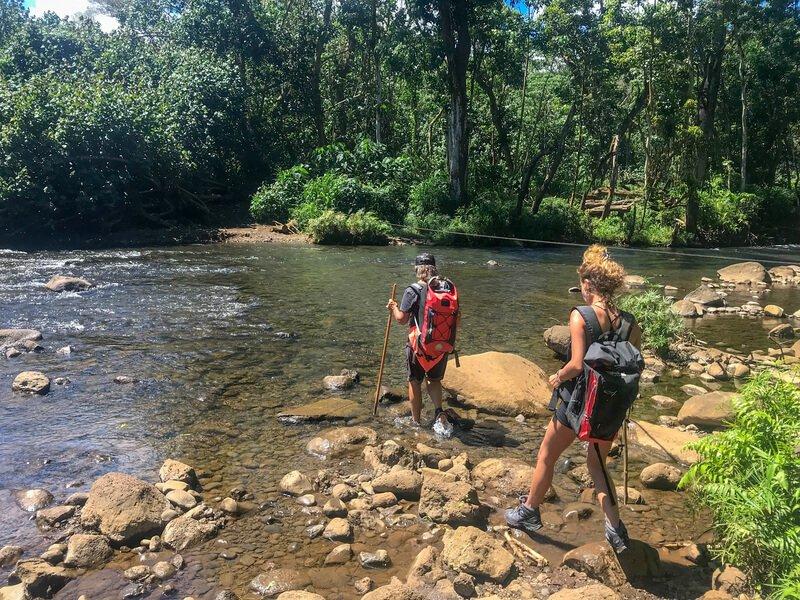 Two woman crossing river hiking to Sacred Falls Kauai